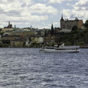 Vy över stadsdelen Södermalm i Stockholm, med Riddarfjärden och en båt i förgrunden.
