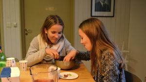 Två unga flickor sitter vid ett bord och sticker ner händerna i en skål med godis.