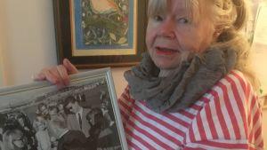 Journalisten Leena Larjonko poserar med fotografi över Alfred Hitchcocks besök i Finland