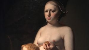 En barbröstad kvinna håller ett gulklot i sin hand.