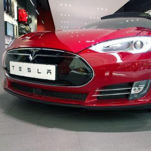 En röd Tesla-bil sedd framifrån.