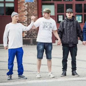 Fem unga personer klädda i hiphop-kläder håller varandra i händerna framför ett gammalt lokstall.