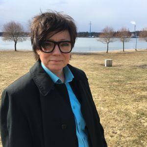 Anneli Jäderholm står vid universitetsstranden i Vasa. Hon har en svart kappa på sig och en blå skjorta. Hon bär stora svartskalmade glasögon och har medellångt mörkt hår.