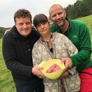 Michael Björklund, Ia Asén och Matias Jungar, fotograferade på en äng. De håller i en plastbunke med lammfärs.