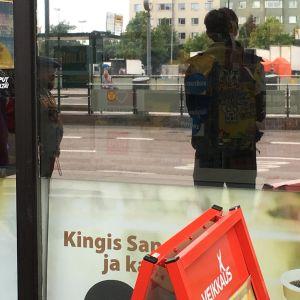 Silhuett av en man speglas i R-kioskens fönster.