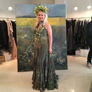 Konstnären Johanna Oras poserar i en grön klänning med blommor.