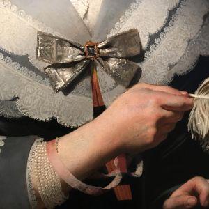 En målning av en dam klädd i spetsklänning och med en fjäder i handen.