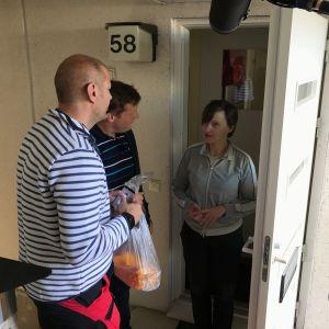 Matias Jungar och Michael Björklund tar emot kantareller i en plastpåse av Maria Holmberg.