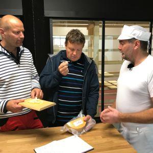 Per-Olof Friman visar upp en ost för Matias Jungar och Michael Björklund.