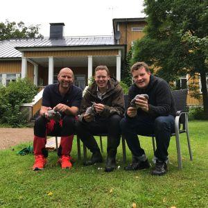 Matias Jungar, Tomas Landers och Michael Björklund sitter på stolar i en trädgård och plockar ringduvor.