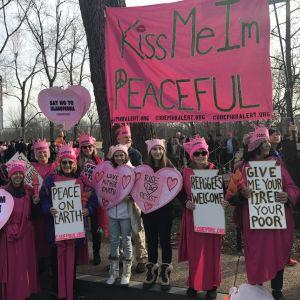 Ann Wright bär en skylt med texten som uppmanar till fred på jorden. Gräsrotsorganisationen heter Code Pink.