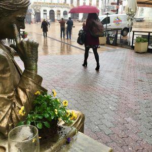 En kvinna går förbi en staty av en man som ser ut att titta på henne bakifrån