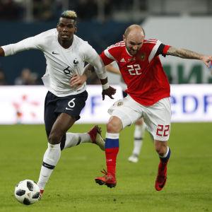 Paul Pogba, till vänster, och tyskfödde ryske landslagsspelaren Konstantin Rausch, kämpar om bolllen i matchen mellan Frankrike och Ryssland den 27 mars 2018.