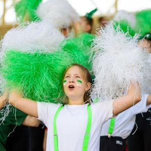 Cheerleading på stafettkarnevalen, ungdomar med vita och gröna pom-poms