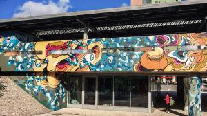 Värikäs seinämaalaus Martinlaakson juna-aseman julkisivussa.