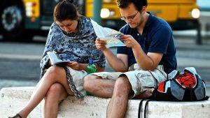 Turistit tutkivat sanakirjaa ja karttaa