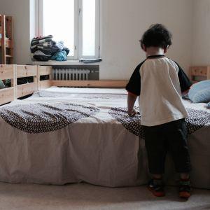 Pojke står vid säng och leker.