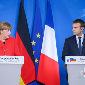 Tysklands förbundskansler Angela Merkel och Frankrikes president Emmanuel Macron tittar på varandra bakom varsitt podium med Tysklands, EU:s och Frankrikes flagga i bakgrunden.