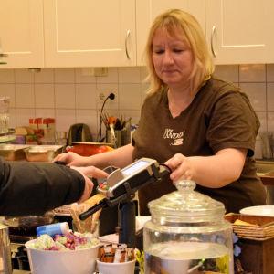En kund betalar i kassan till cafébiträdet Marika Sontag.