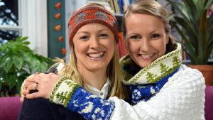 Elin Skagersten-Ström ja Lee Esselström ja neulotut Suomi 100 -asusteet.