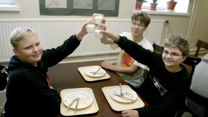 Kouluruokailu, pojat skoolaavat maitolaseilla.