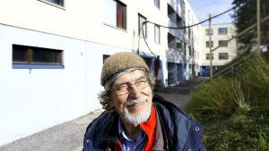 Mauri Tahvanainen hymyilee taloyhtiön pihalla.