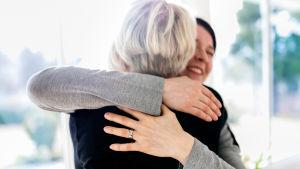 Kaksi naista halaa toisiaan.