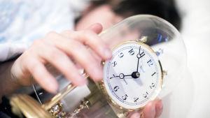Nainen nukkuu kellon kanssa