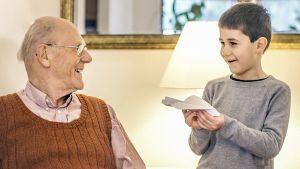 Vasemmalla vanhempi mies katsoo oikealla seisovaan nuoreen poikaan, jolla on paperilennokki kädessään. Molemmat hymyilevät.