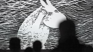 Muumi-aiheinen animaatio konferenssin näytöksessä valkokankaalla, yleisöä (siluetti).