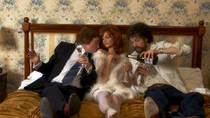 Kolme ihmistä nojaa seinään sängyllä. Keskellä nainen, sivuilla kaksi miestä. Toinen kaataa kuoharia lasiin.
