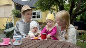 Familj sitter vid ett bord utanför sin kolonistuga.