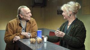 André Wilms ja Elina Salo baaritiskin molemmin puolin. Kuva Aki Kaurismäen elokuvasta Le Havre.