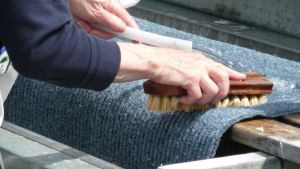 En hand som håller i en skurborste och tvättar en matta.