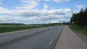 En asfalterade väg med åker på ena sidan och träd på andra. Trafikmärke för förkörsrätt. Telefonstolpar. Sommar, blå himmel med moln.