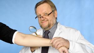 Man i läkarrock undersöker huden på en annan persons arm med förstoringsglas