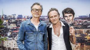 """Anders Glenmark och Thomas """"Orup"""" Eriksson i närbild med stockholm i bakgrunden. Orup håller i ett paffansikte av Niklas Strömstedt."""