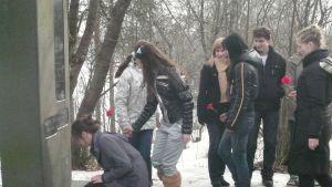 Ungdomar placerar blommor på Edith Södergrans grav