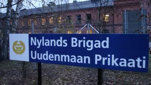 En skylt där det står Nylands Brigad, i bakgrunden en tegelbyggnade på Dragsviksområdet i Ekenäs.
