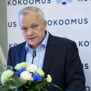 Samlingspartiets riksdagsgrupps ordförande Kalle Jokinen står vid en talarstol i närbild med Samlingspartiets banderoll bakom sig.