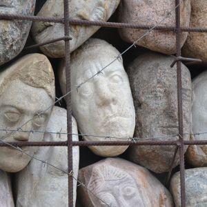 Ansikten av sten bakom taggtrådsgaller, ett minnesmärke över offren för kommunisttidens förtryck