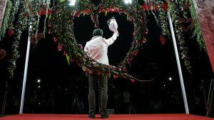 Japansk man med ryggen mot kameran håller en blombukett i luften.