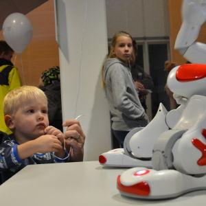 liten ung blond pojke leker med hälsorobot på teknikdagar i Åbo.