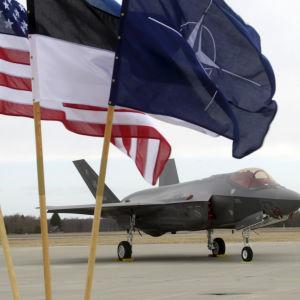Ett F-35 jaktplan i Estland. I förgrunden står USA:s, Estlands samt Natos flagga.