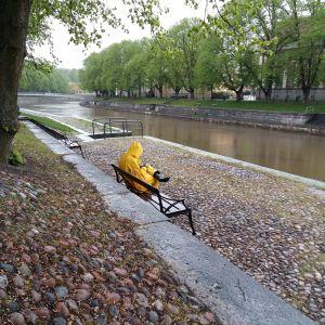 En person sitter i ösregn i gula regnkläder på en parkbänk vid Aura å, i ett Åbo som i övrigt är helt tomt.