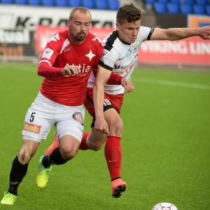 Aleksi Ristola (till höger) kämpar om bollen mot HIFK:s Jukka Sinisalo under lagens ligamatch tidigare i år. Nu byter också Ristola till den röda tröjan.