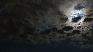 Natthimmel med moln och fullmåne.