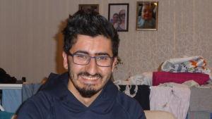 Profilbild på Aras Muhilden han sitter i soffa i bakgrunden tvätt på tork och fotografier på hans barn