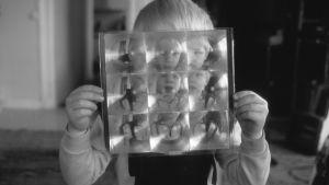 Barn som håller upp en bild med många barnansikten.