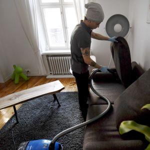 Städaren  Bayron Boloyi dammsuger soffan ett privat hem i Helsingfors i mars 2018.